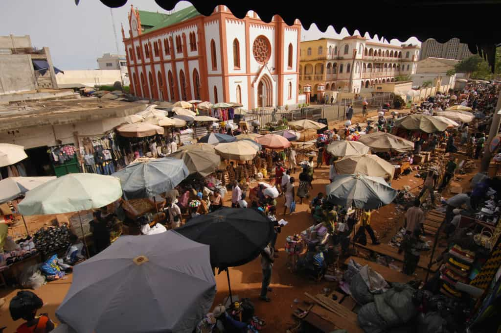 The Grand Market in Lome, Togo is in front of a large white and rust colored church. The vendors have large umbrellas over their wares and people are crowding the walkway between them.