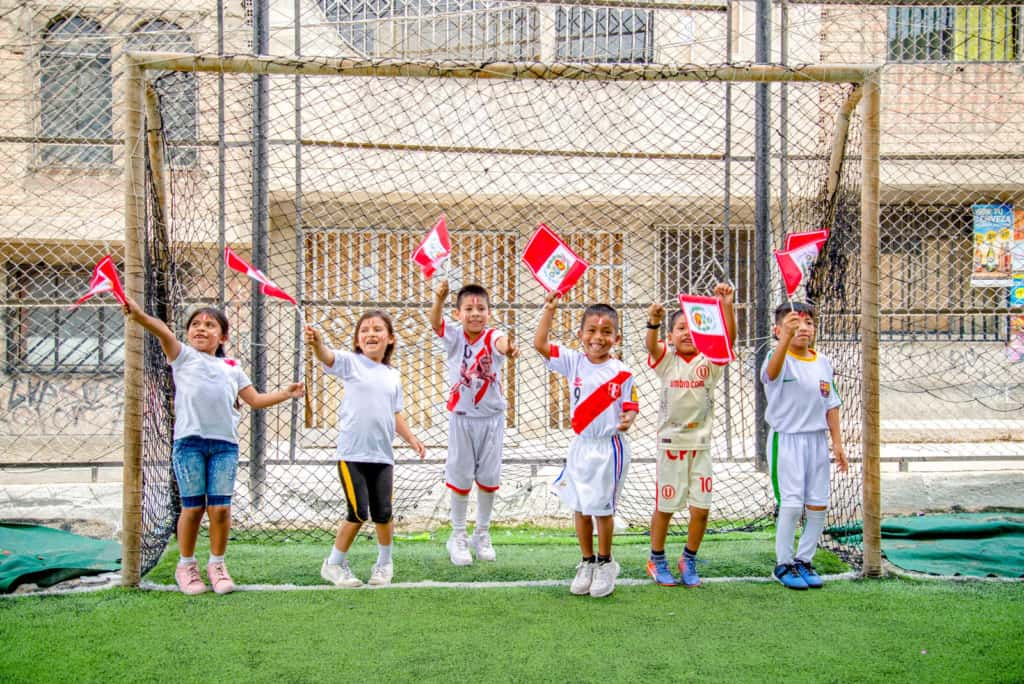 A group of children holding, waiving Peru flags. They are standing, jumping on green grass, a green soccer field. They are laughing and smiling. A soccer goal and buildings are in the background.