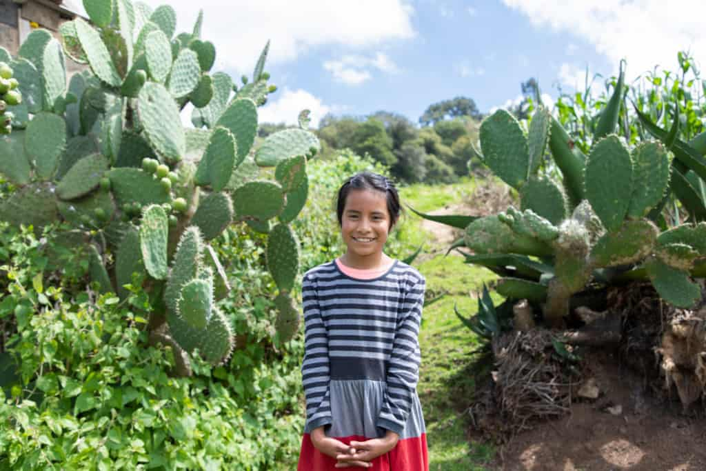 Girl standing in the middle of two cactus, demonstrating that she was victorious over the thorns of death. She is wearing a blue and black striped shirt, and smiles at the camera.