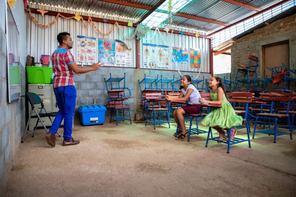 Girl wearing a green dress and pink sandals and is sitting with a friend, wearing a white shirt, a red skirt and black sandals. They are sitting in one of the newly constructed classrooms of a Compassion center. The project tutor is in the front of the classroom, wearing a red plaid shirt and blue pants.