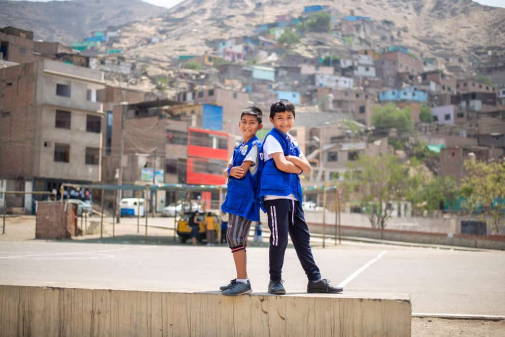 Two boys standing back-to-back with their arms crossed. An empty cement basketball court and apartment building are in the backgroud.