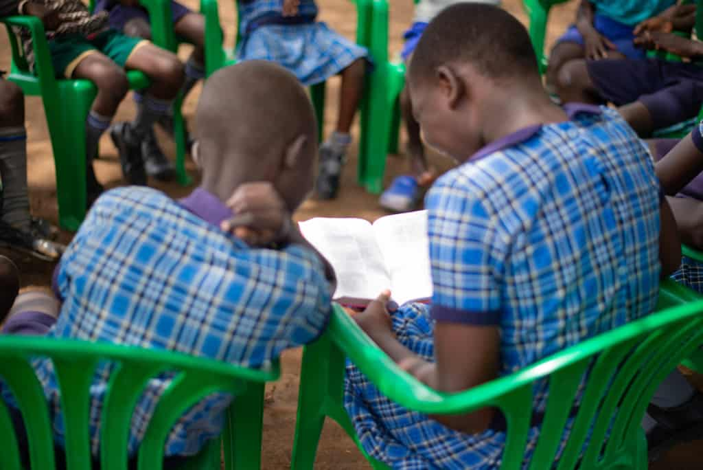 Rita and several other children are sitting outside in green plastic chairs. They are reading the Bible together and they are all wearing their school uniforms, blue plaid dresses.