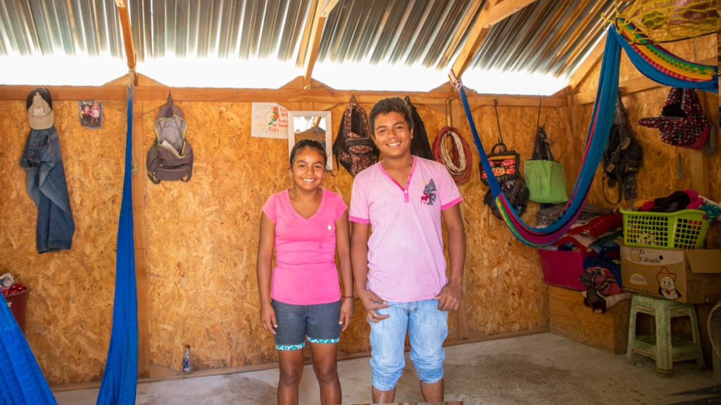 Girl wearing a dark pink shirt and her brother is wearing a light pink shirt. They are standing in their home between the hammocks they use during the day and at night to sleep.