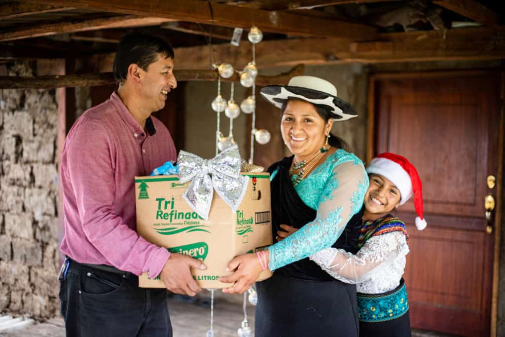 Miguel is giving a food box to Jenny while Joselin hugs her mother. They are wearing traditional clothes. There are Christmas lights behind them.