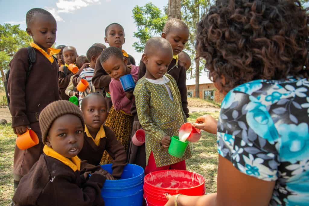 Kindergarten students at Ekenywa Pre and Primary English Medium School are in a line being served porridge by their teacher. The students are wearing brown sweaters and are outside.