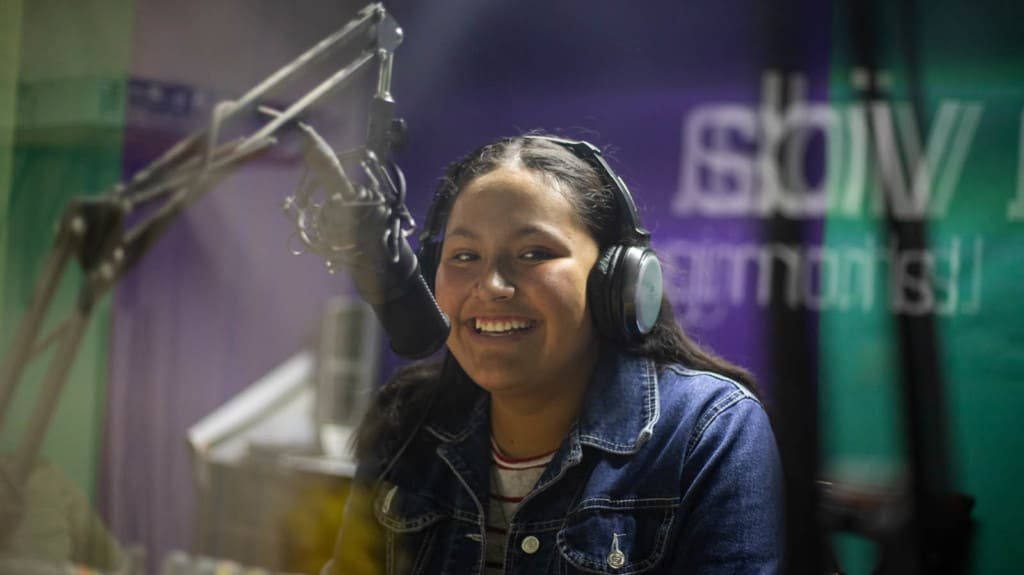 Itzel is wearing a jean jacket and headphones. She is speaking into the microphone during her radio show.