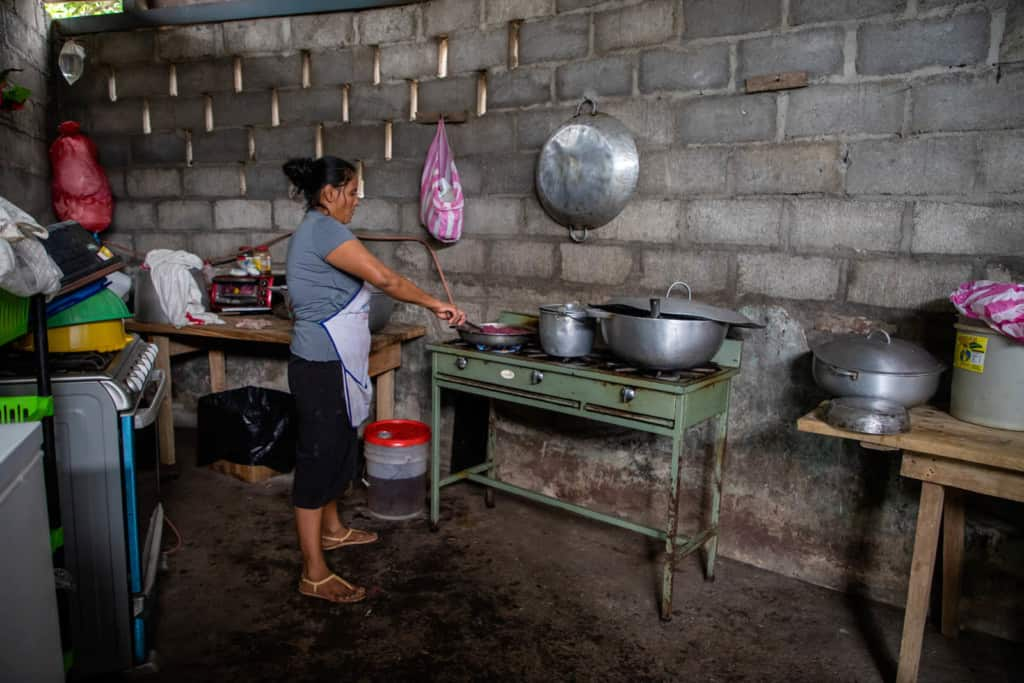 Woman wearing a grey shirt and a black skirt, and is preparing lunch for the Compassion beneficiaries. To help the kids gain weight, the nutritionist instructed the center to give them food that was high on protein and carbohydrates such as rice, beans, eggs and plantains.