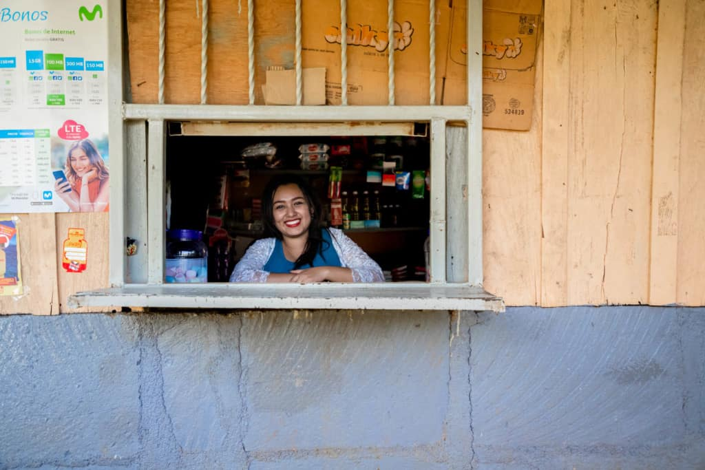 Woman standing inside her house, and leaning against the edge of the window from which they sell food, canned goods, candies and drinks like sodas and orange juice. She is wearing a blue shirt and a white cardigan while looking directly at the camera and smiling.