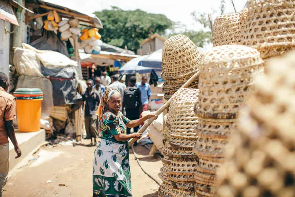 A woman in a green and white dress with a scarf on her head holds a stick over stacks of woven baskets at a market. There are more people walking in the background.