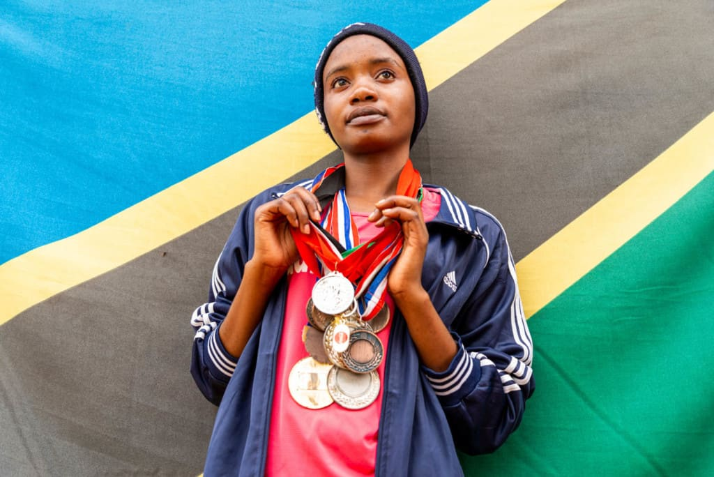 Clenzeensia, in a hot pink shirt and navy blue jacket and cap, is standing in front of the Tanzanian flag with her medals hanging from ribbons around her neck.