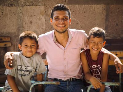 A pastor of a church in Nicaragua wears a pink button-down shirt and smiles as he sits next to two smiling young boys