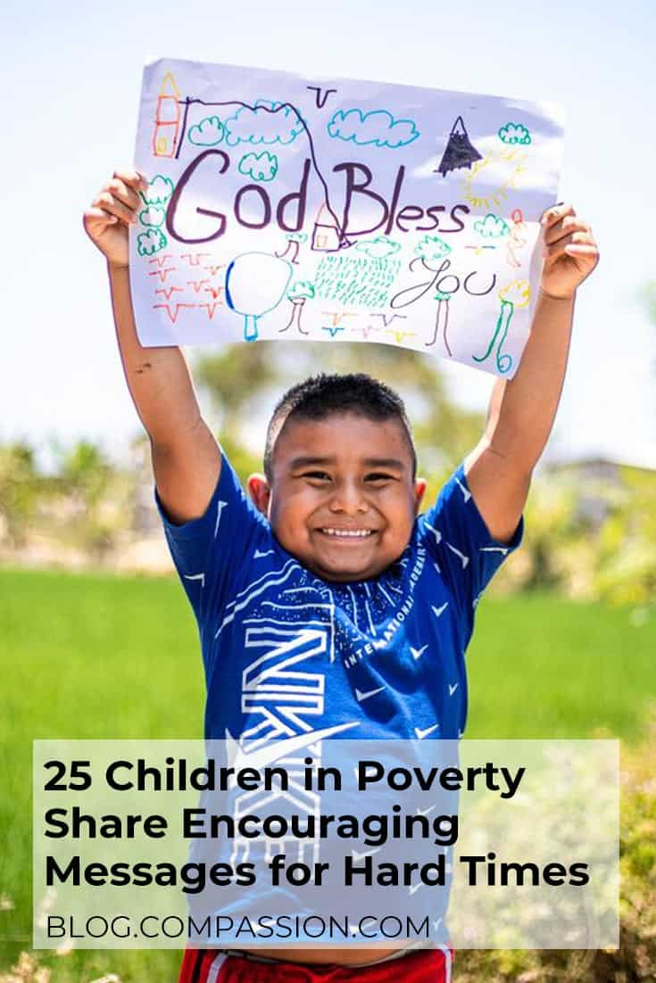 Young boy with a big smile holding a sign that says God bless you.