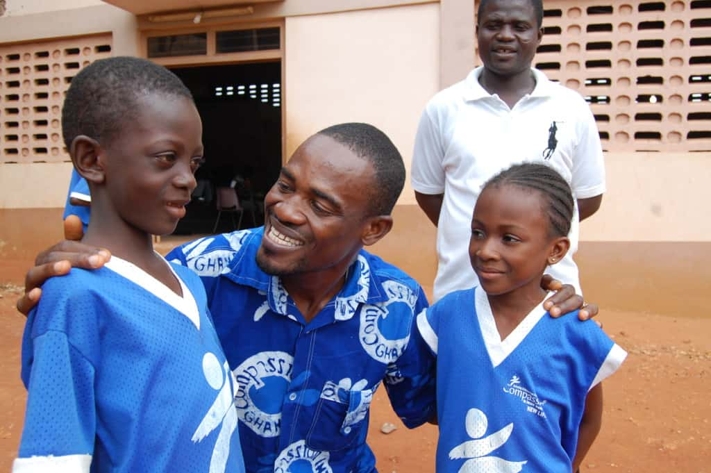 A Compassion center worker in Ghana engages with two young children. They are all wearing blue Compassion logo shirts