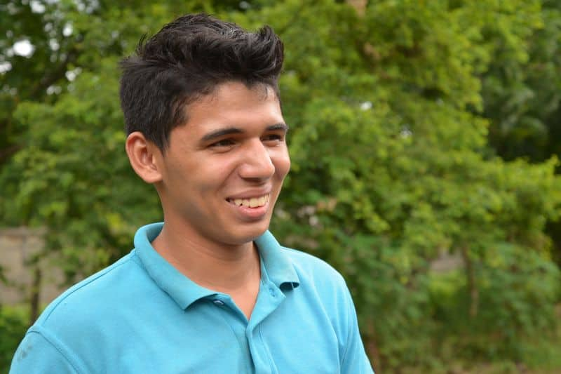 Junior, a teenage boy, smiles. He is wearing a blue polo shirt. Green trees are behind him