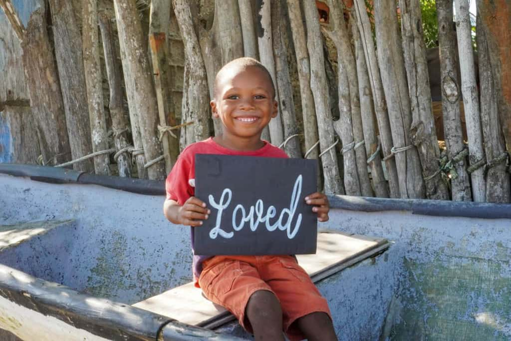 """A boy is in his community and is sitting on a small ship on the beach. He smiles while holding a poster that says he is """"loved"""" at the Compassion center."""