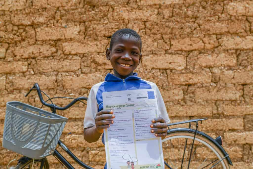 Boy wearing a blue shirt with white sleeves. He is standing in front of his bike and is holding a letter he received from his sponsor. Behind him is a tan brick wall.