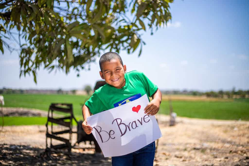Gino is wearing a green shirt and jeans. He is standing outside with a rice field behind him and he is holding a sign that says Be Brave.