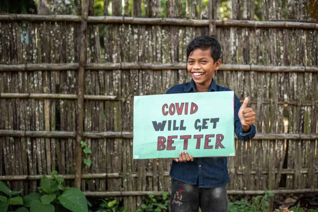 "Bikash is wearing a navy blue shirt and jeans. He is holding a green sign that says, ""COVID will get better."" He is standing in front of a wooden fence and is giving a thumbs up sign."