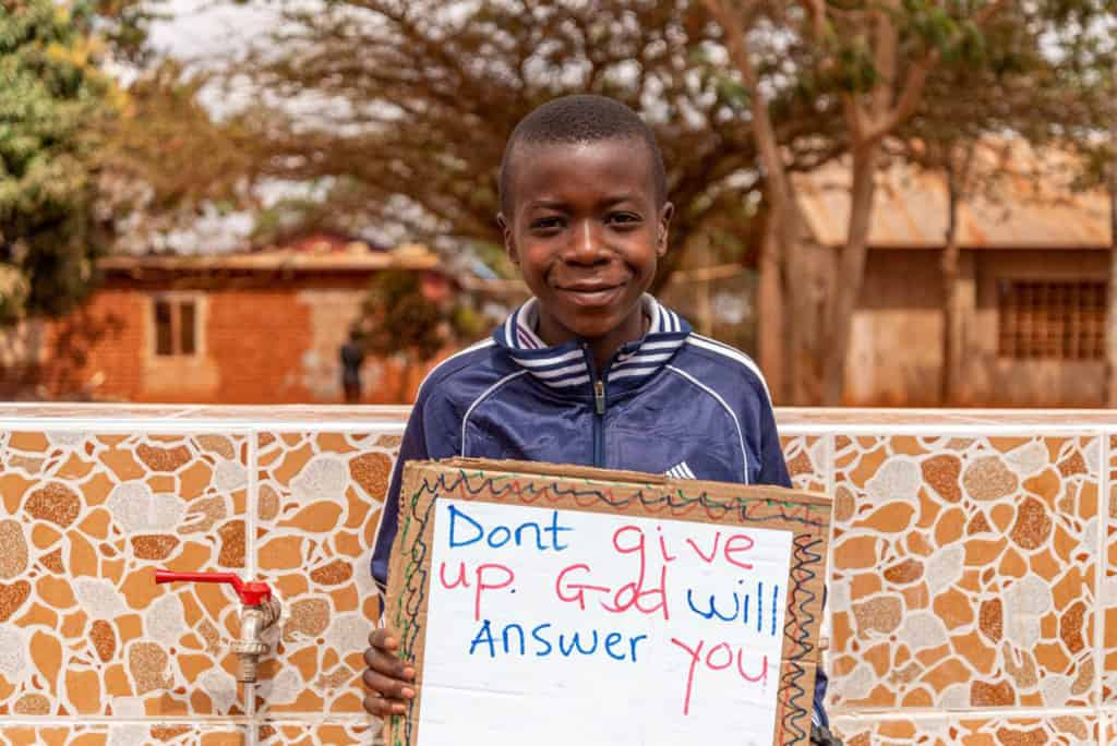 "John is wearing a blue jacket and is holding up a sign that says, ""Don't give up. God will answer you."""