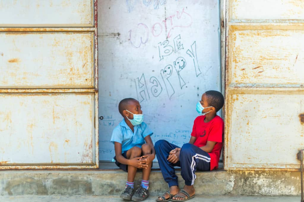 "Charles is wearing a blue shirt. He is sitting with his friend, Emmanuel, wearing a red shirt and blue pants. They are sitting in front of a sign that says, ""Don't worry, be happy."" Both boys are wearing face masks."
