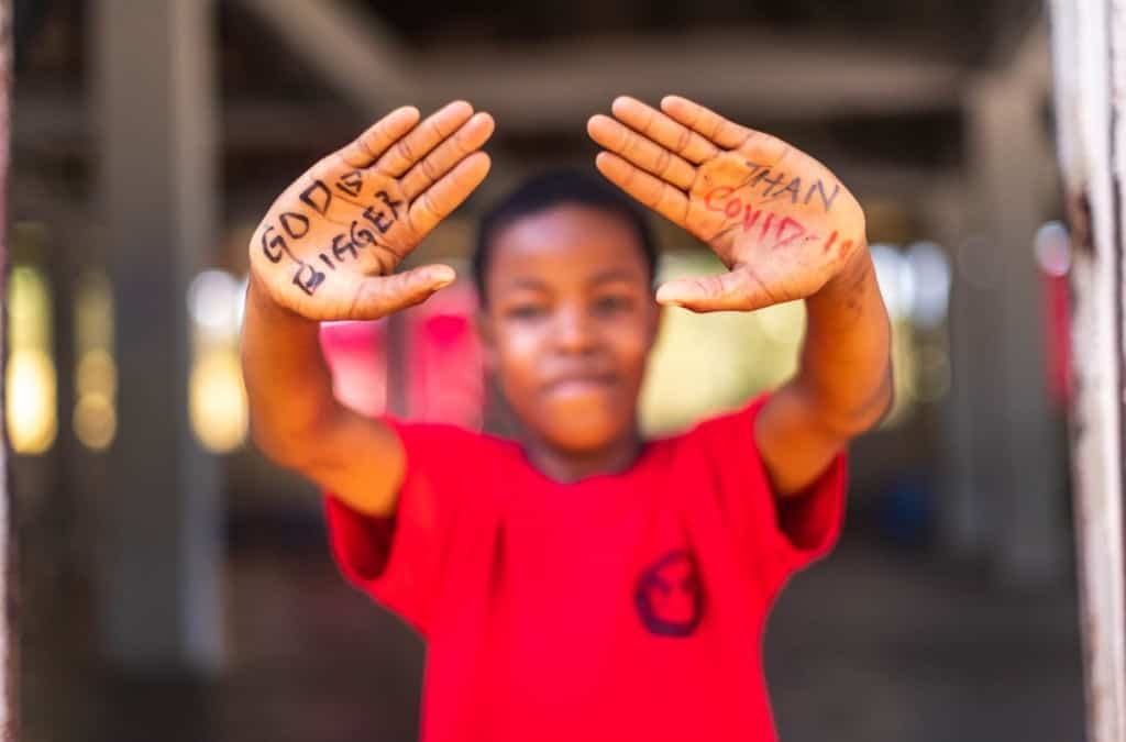 "Emmanuel is wearing a red shirt. On his hands is written ""God is bigger than COVID-19."" He is holding his hands out toward the camera."