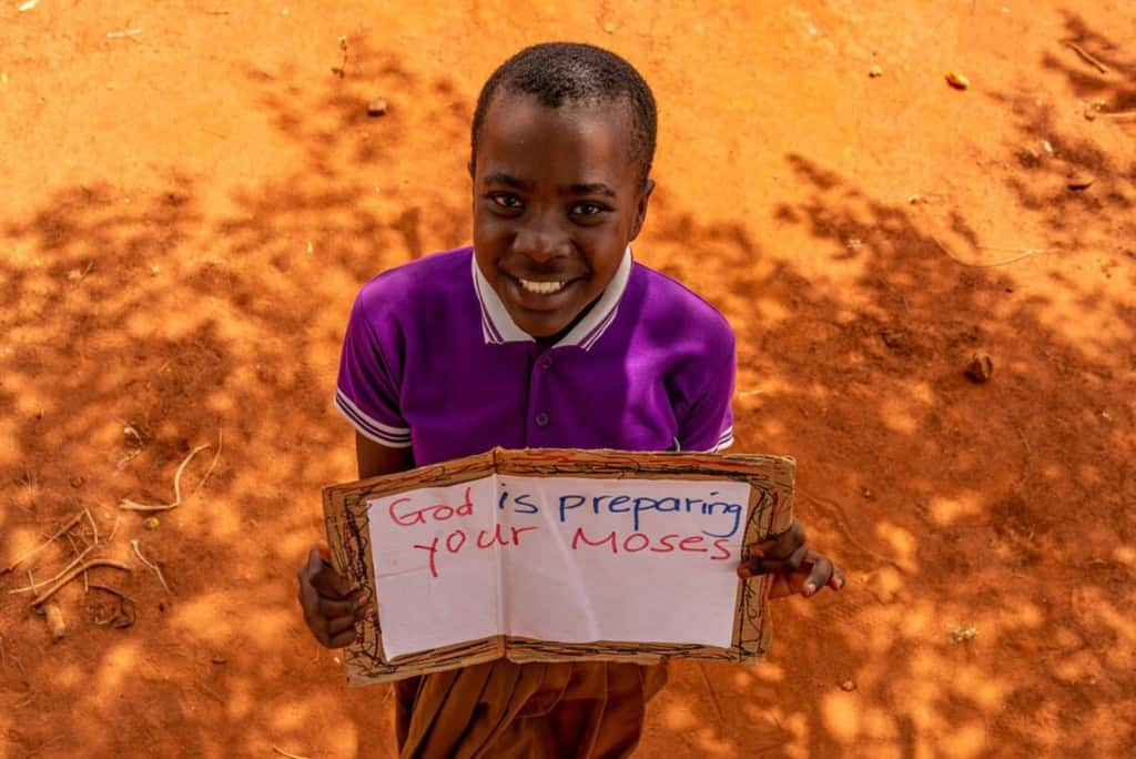 "Zawadi is wearing a purple shirt and a tan skirt. She is standing outside and is holding a sign that says, ""God is preparing your Moses."""