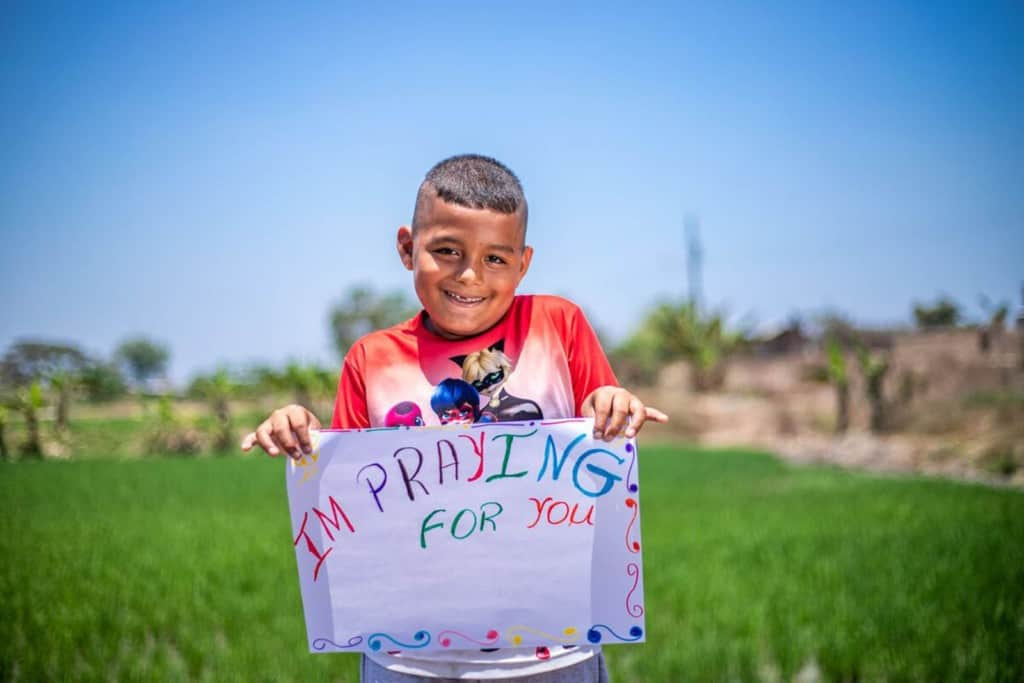 Caleb is weairng a white shirt with a pattern on the front and red sleeves. He is standing outside with a rice field behind him and is holding up a sign that says I'm Praying For You.