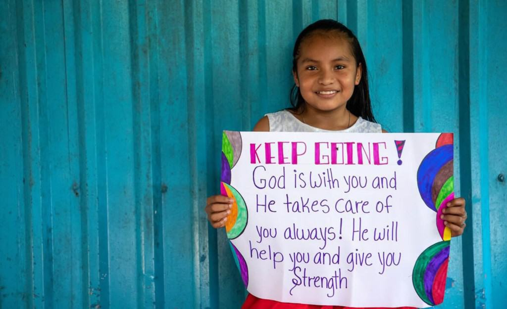 Fatima is holding up a sign that says: Keep going, God is with you and He takes care of you always! He will help you and give you strength. She is standing in front of a blue metal wall at the Compassion center.