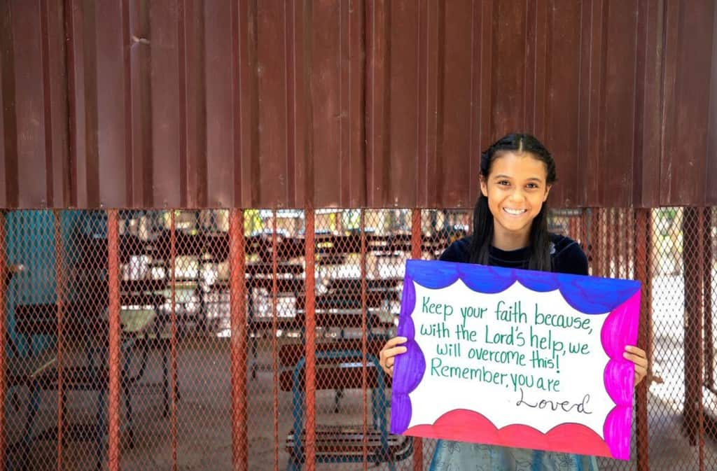 Josebeth is wearing a black shirt and is holding up a sign that says: keep your faith because, with the Lord's help, we will overcome this! Remember, you are loved! She is standing in front of a brown wall at the Compassion center.