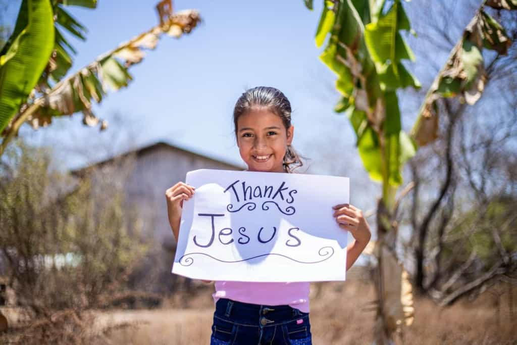 Haydee is wearing a pink shirt and jeans. She is standing outside her home and is surrounded by banana trees and is holding a sign that says Thanks Jesus.