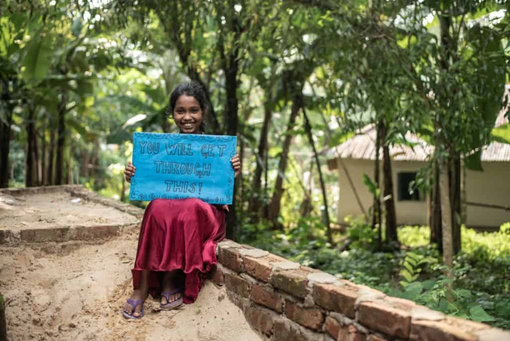 "Sumona is wearing a dress with a floral bodice and a red skirt. She is sitting down on a short brick wall and is holding a blue sign that says, ""You will get through this."" There are trees and a house behind her."