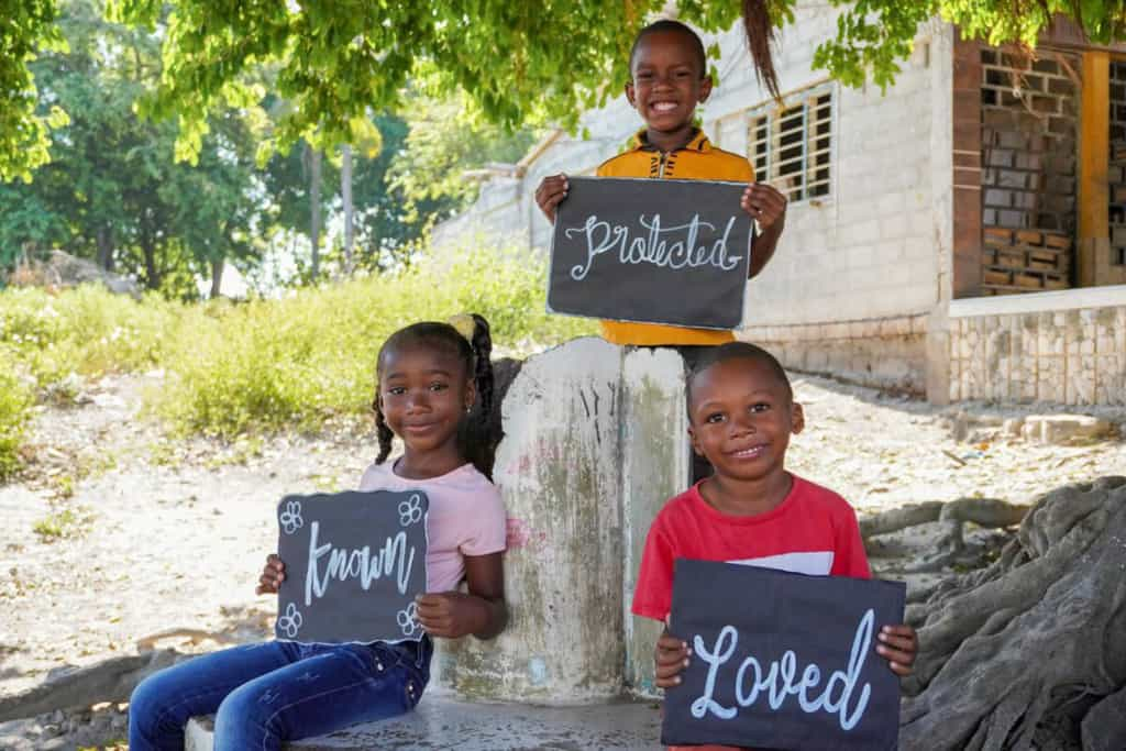 Three children in their community on the island where they live. They are holding posters to show they are known, loved, and protected at their Compassion center.