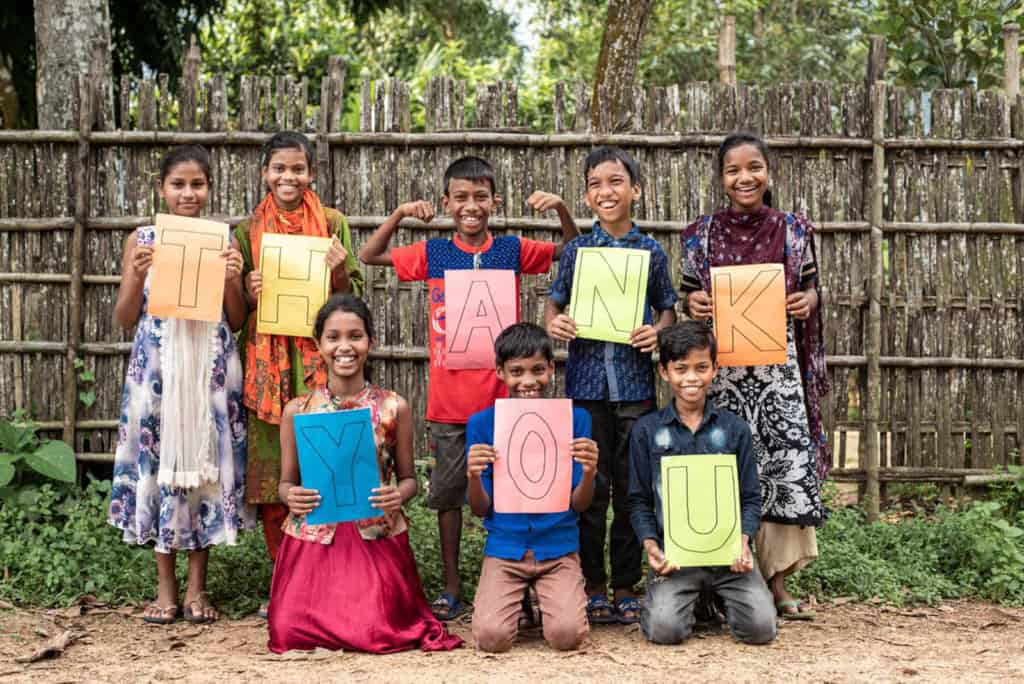 A group of children are holding up letters on colorful paper that spell out Thank you. They are in front of a wooden fence.