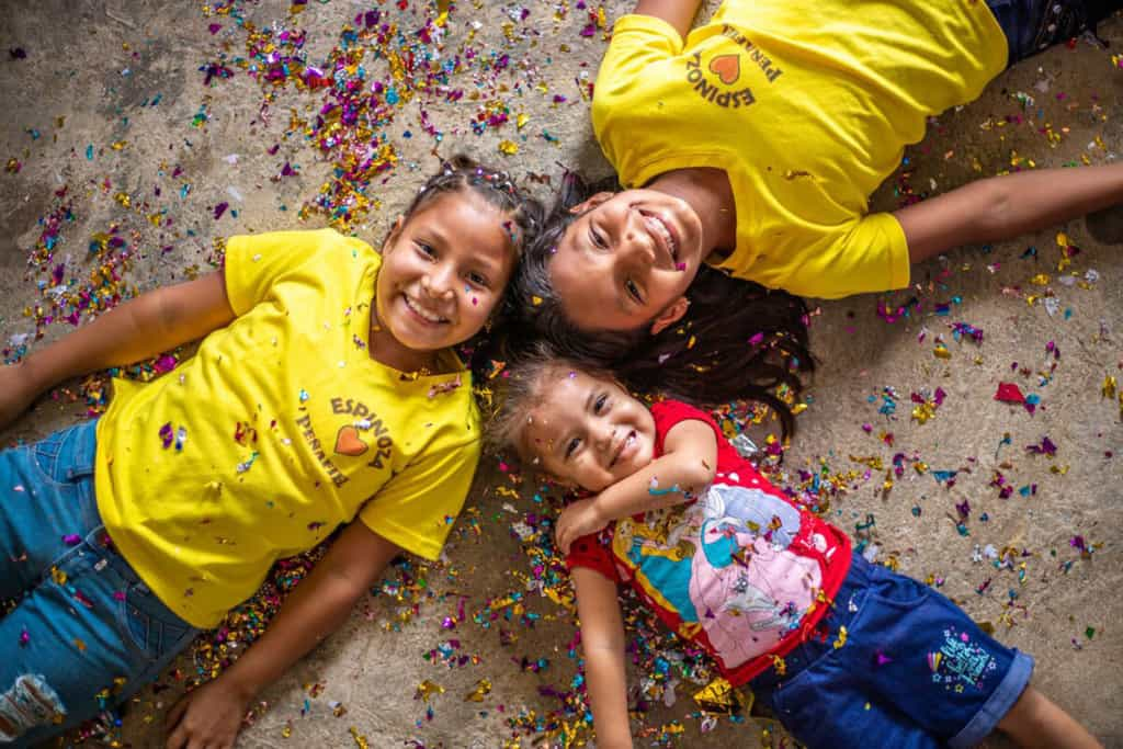 Ashley and Emily are wearing yellow shirts and jeans. They are laying down with their younger sister, Dara, wearing a red shirt and jean shorts. THey are laying in confetti with their heads together.