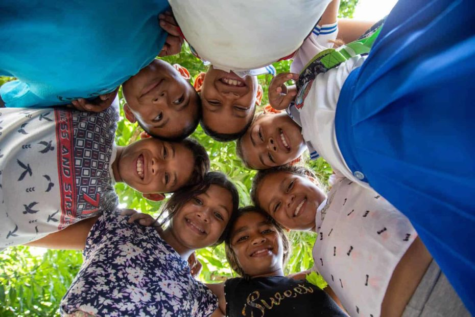 A group of beneficiary children are standing outside with their heads together and are looking down at the camera.