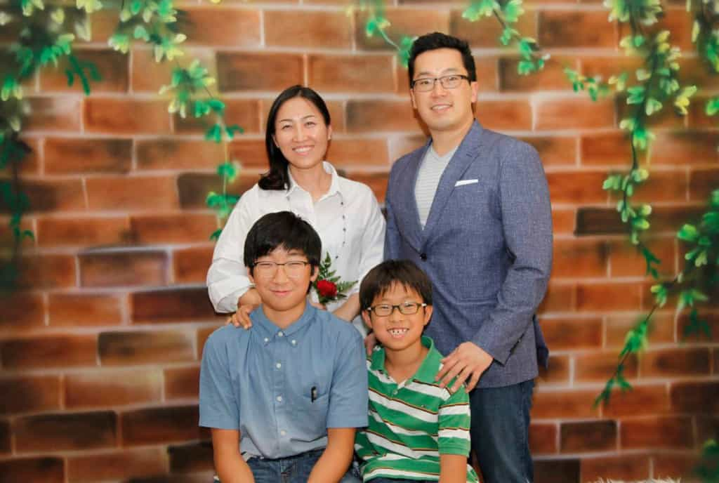David Choi and his family posing in front of a painted wall.
