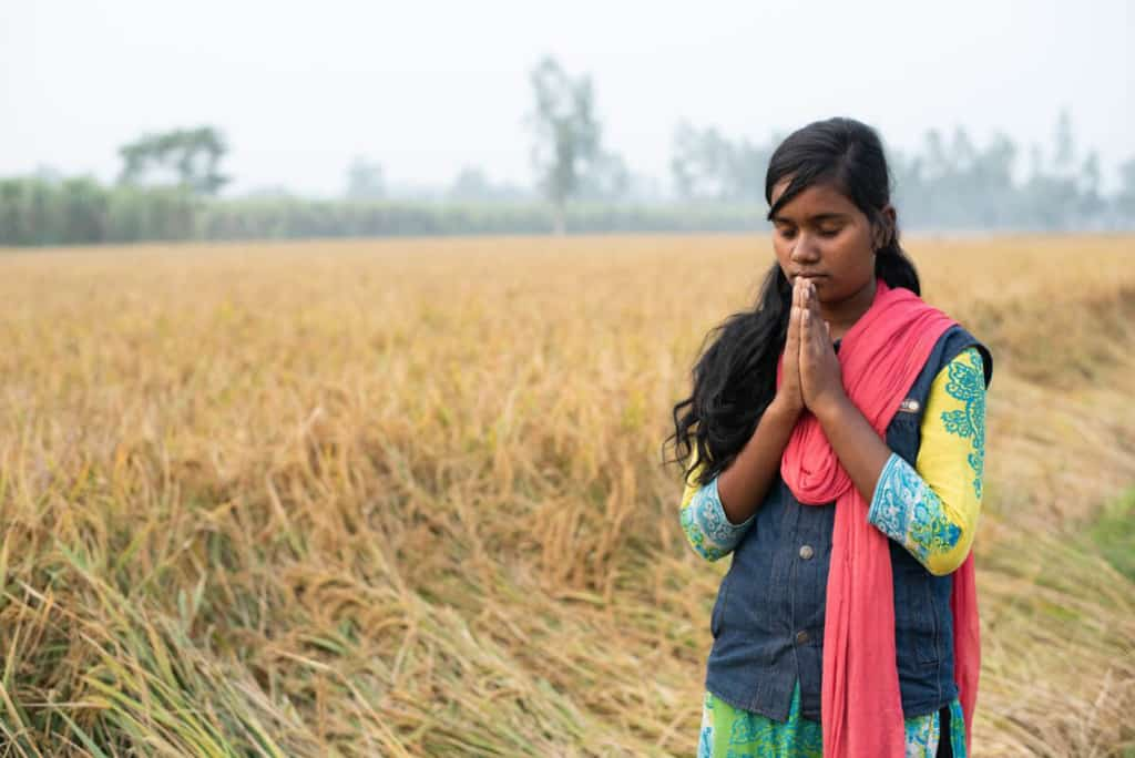 Girl in a yellow, green and blue dress, blue vest, and red, pink scarf, stands in a field of tall grass with her eyes closed and hands held together in front of her, praying. There are trees in the background.