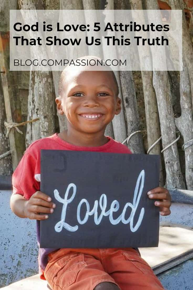Boy holding a chalkboard with the word loved written on it