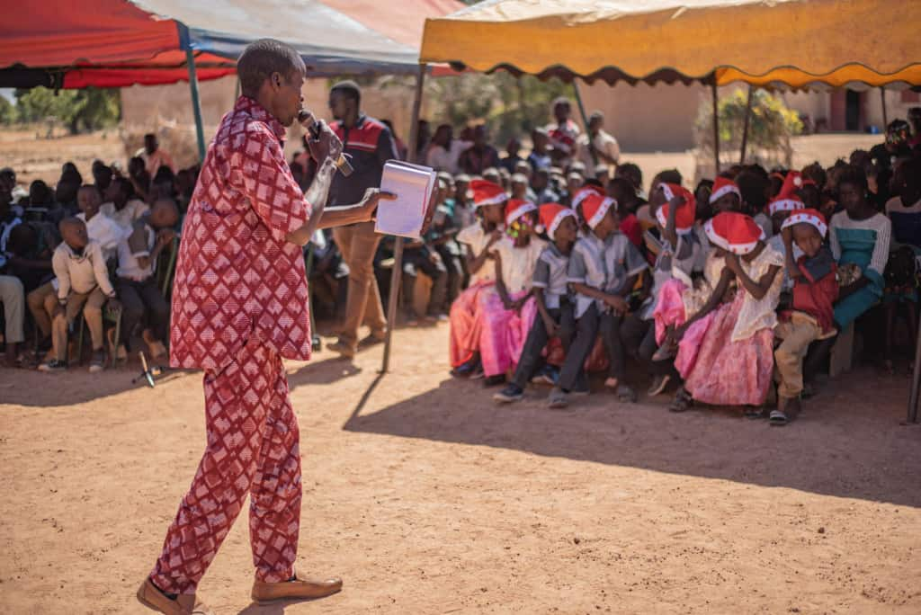 The pastor, in red, is preaching the gospel to the beneficiaries and guests at the ceremony outside the church compound. He is holding a Bible, a notebook and a microphone. A group of children wearing red and white Santa hats are sitting in the shade under a tent.