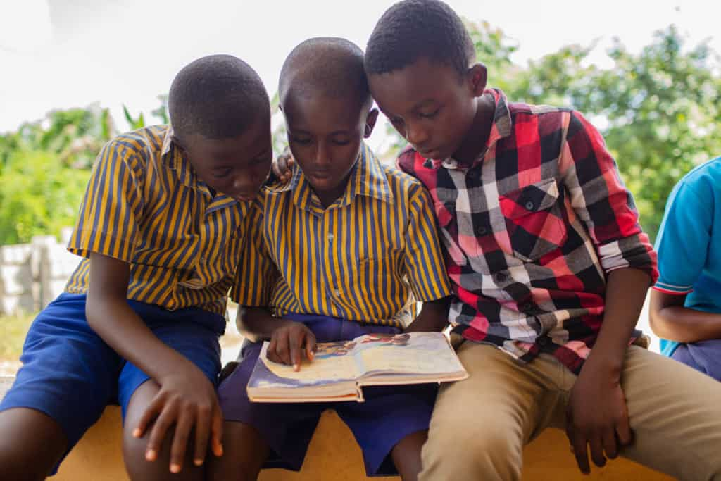 Children in purple, blue and yellow uniforms and a black and red shirt are sitting together reading an illustrated Bible.