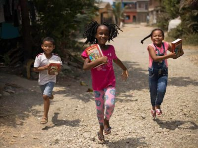 Samuel, in a white shirt, María Salome, in a fuchsia t-shirt, and Maria Angelica, in denim overalls, are running home along a dirt, gravel road while holding the Illustrated Bibles they received at the project.