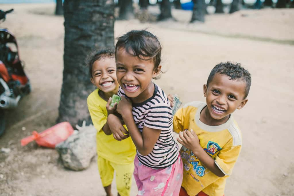 Girl, in a pink and black shirt, is standing on the sand laughing with another girl and a boy, both wearing yellow. Julenda is not part of the Child Sponsorship Program. There are trees in the background.
