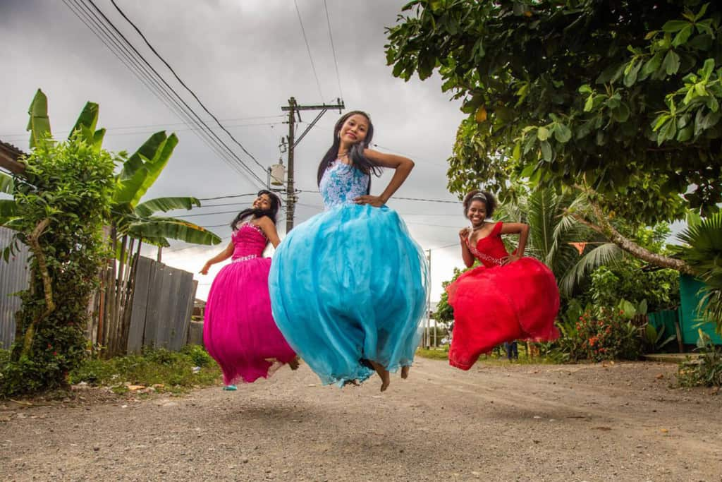 Lesly, wearing a blue dress, is with her friends, Ledis, wearing a pink dress, and Celena, wearing a red dress. They are all jumping in the air outside the project. There are trees behind them.