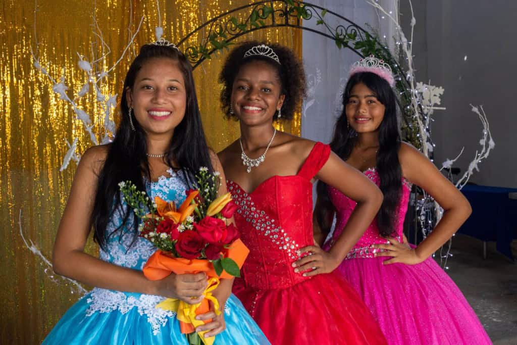 Lesly, wearing a blue dress, Celena, wearing a red dress, and Ledis, wearing a pink dress are standing together at the Compassion project. There is a gold curtain behind them.