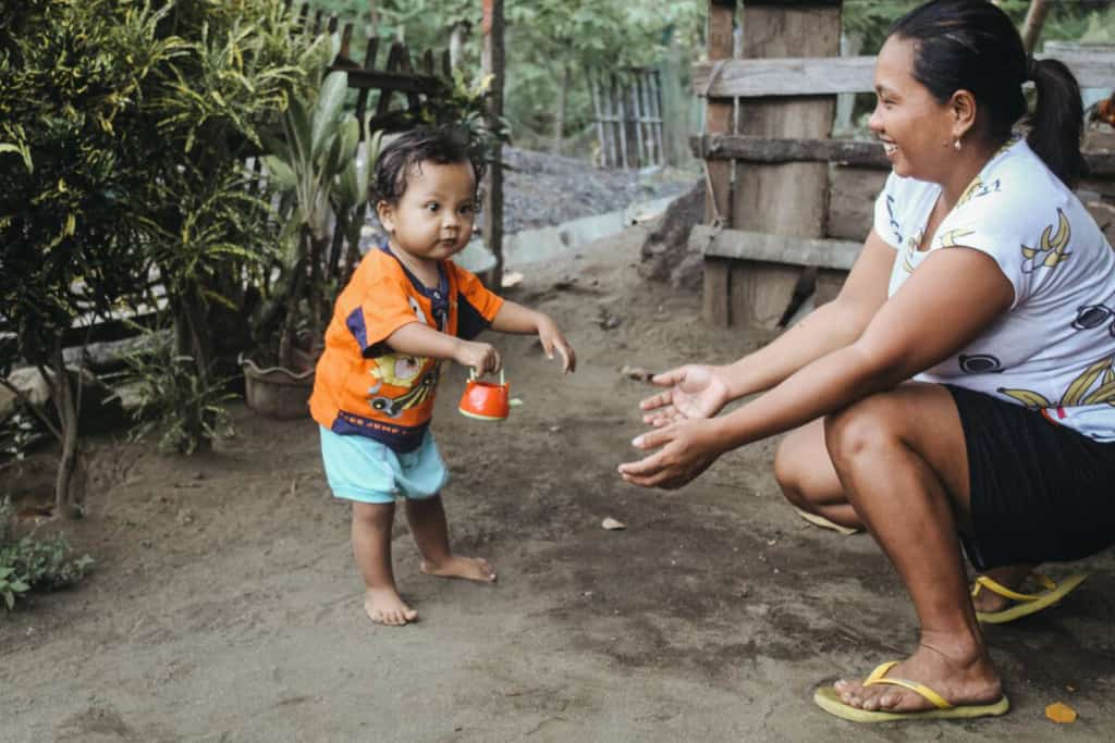 Toddler is wearing light blue shorts and an orange shirt. His mother is wearing black shorts and a white shirt. She is kneeling down with her arms outstretched helping him walk. Behind them is a fence.