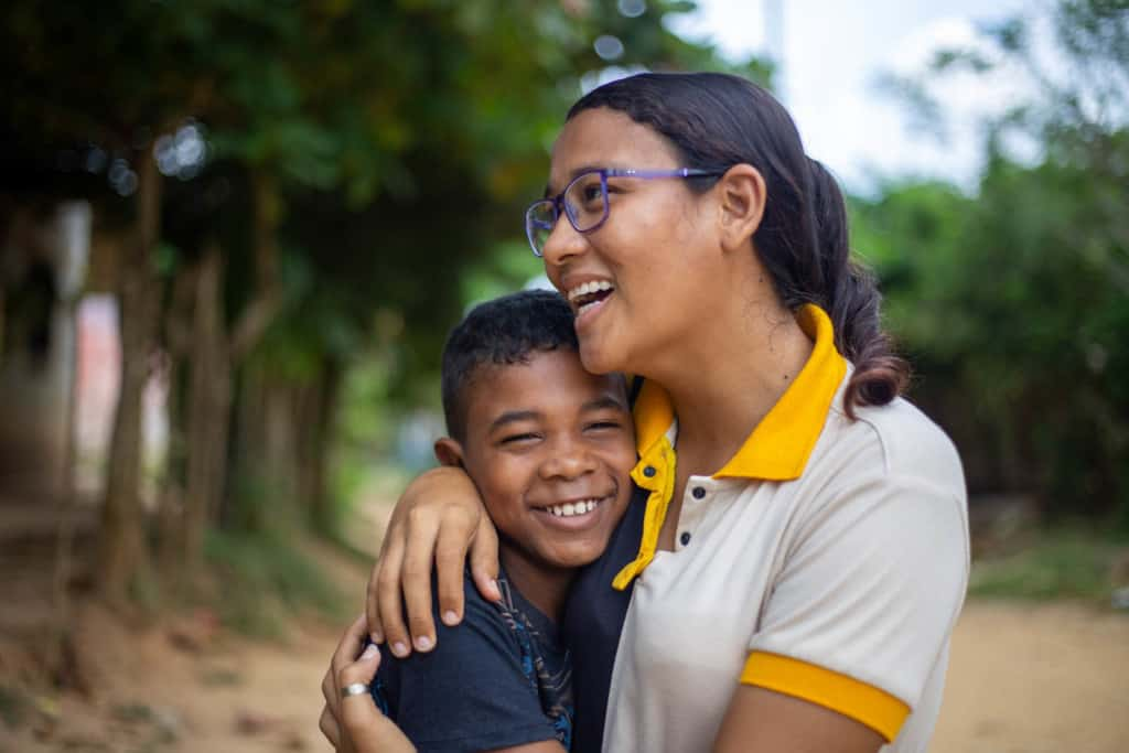 Project tutor is visiting a student as part of her duties at the Compassion program. She just arrived at his home and they are hugging.