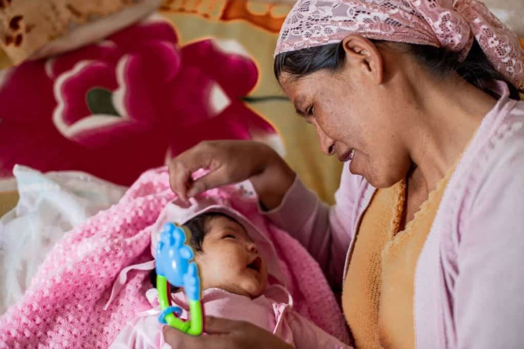 Woman holding her baby who is wearing pink. They are playing with a rattle.