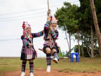 Abo (left, standing) is pushing Kanyaporn (right) on an Akha traditional celebration swing. They are wearing their traditional clothing and there are trees in the background.