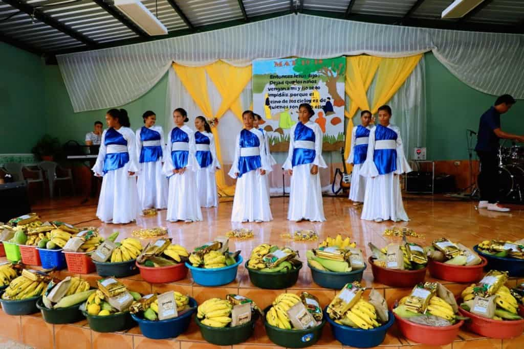 Girls aged 13-15 years old are wearing white and blue worship dancewear. They are performing on the church stage.