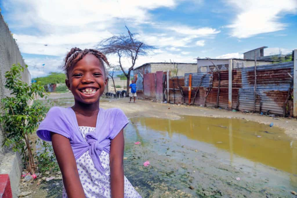 A smiling girl wearing a purple outfit sits in an impoverished neighborhood